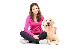 新女性摆在与拉布拉多猎犬 免版税库存图片