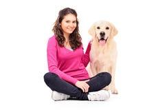 新女性摆在与狗 免版税库存图片