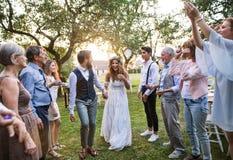新娘、新郎和客人结婚宴会的外面在后院 库存图片