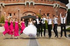 新娘、新郎和朋友跳在老fo的前面的身分 免版税库存照片