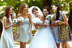 新娘与摆在公园的女傧相谈话 图库摄影