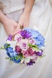 新娘举行色的青桃红色婚礼花束 免版税库存图片