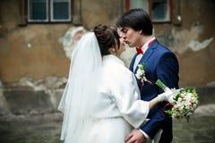 新娘倾斜给站立的亲吻的一个新郎在老后院 免版税库存照片