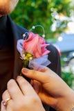 新娘别住一朵钮扣眼上插的花对groom& x27; s水兵 图库摄影