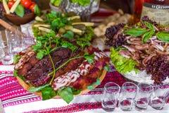 新娘和他们的客人的婚姻的自助餐 与塔帕纤维布酒吧的表用被治疗的肉,用其他开胃菜 库存照片