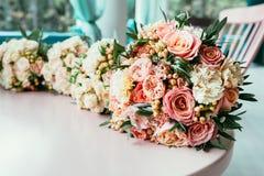 新娘和女傧相婚礼花束在桌上在ceremo前 免版税库存图片