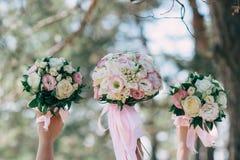 新娘和她的朋友在手上拿着他们的婚礼花束 库存图片