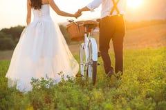 新娘和新郎与一个白色婚礼骑自行车 免版税图库摄影