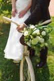 新娘和新郎与一个白色婚礼骑自行车 免版税库存图片