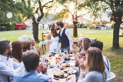 新娘和新郎与客人结婚宴会的外面在后院 库存照片