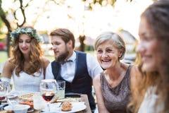 新娘和新郎与客人结婚宴会的外面在后院 免版税库存照片