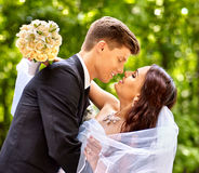 新娘和新郎与室外的花 免版税库存图片