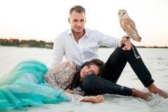 新娘和新郎与小猫头鹰在沙漠坐白色沙子背景  特写镜头 库存照片
