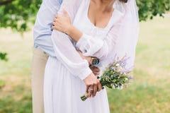 新娘和新郎与淡紫色花束 库存图片