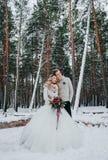 新娘和新郎与花束在冬天森林冬天婚礼的背景摆在 附庸风雅 库存照片