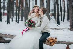新娘和新郎与花束在多雪的森林冬天婚礼摆在 附庸风雅 免版税库存照片