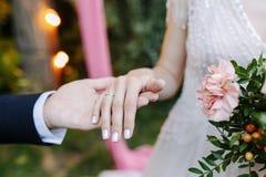 新娘和新郎交换圆环在婚礼,一个婚礼期间在有减速火箭的电灯泡的夏天绿色庭院里 库存图片