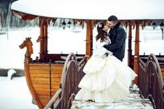 新娘和新郎亲吻在一条木小船的前面盖与 免版税库存图片