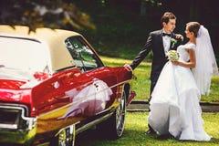 新娘和新郎亲吻在一辆开放葡萄酒汽车的身分 免版税图库摄影
