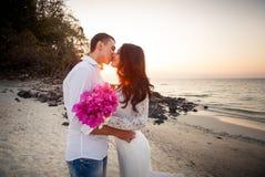新娘和新郎亲吻在海滩在黎明 免版税库存照片
