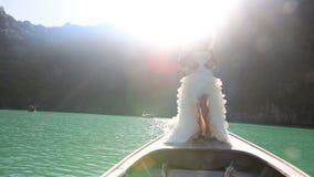 新娘和新郎亲吻在longtail小船的身分在背后照明 股票录像