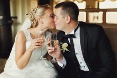 新娘和新郎亲吻拿着葡萄酒杯用在他们的香槟 免版税库存图片