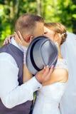 新娘和新郎亲吻的掩藏在帽子后 免版税库存照片