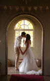 新娘和新郎亲吻的里面教会 免版税图库摄影