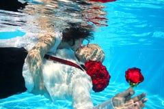 新娘和新郎亲吻的水下的下潜水池水起来了 免版税图库摄影