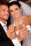 新娘和新郎使叮当响的玻璃 免版税图库摄影