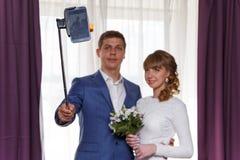 新娘和新郎做selfie 在电话的重点 免版税库存照片