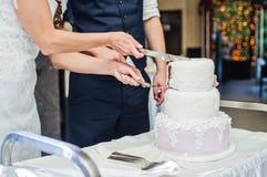 新娘和新郎切了传统婚宴喜饼 免版税图库摄影