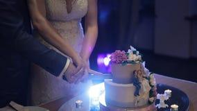 新娘和新郎切他们的婚宴喜饼 股票录像