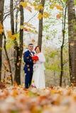 新娘和新郎和落秋叶 免版税图库摄影