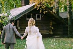 新娘和新郎回森林秋天婚礼的木家 附庸风雅 图库摄影