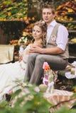 新娘和新郎在一个土气样式坐石步在晴朗的秋天森林,包围通过婚姻装饰 免版税图库摄影