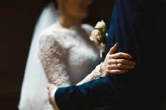 新娘和新郎在一件鞋带礼服和一套服装有一只蝴蝶的与一budoner与米黄和白花,爱的概念 免版税库存图片