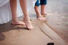新娘和新郎在一套婚礼礼服的` s腿在水中 库存照片