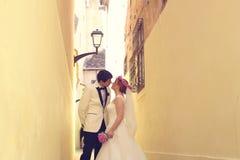 新娘和新郎在一条狭窄的街道上 库存照片