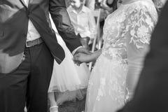 新娘和新郎在一种婚姻的仪式期间的举行手在黑白 库存照片