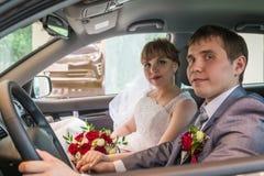 新娘和新郎在一辆汽车在婚礼 免版税库存照片