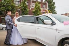 新娘和新郎在一辆汽车附近在婚礼 免版税库存图片