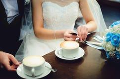 新娘和新郎在他们的婚礼那天,在咖啡馆的饮料咖啡 库存照片