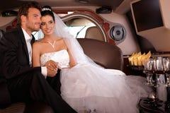 新娘和新郎在大型高级轿车微笑 免版税库存照片