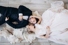 新娘和新郎在婚姻的衣裳在地板和微笑上说谎 免版税库存图片