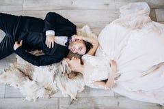 新娘和新郎在婚姻的衣裳在地板和微笑上说谎 免版税库存照片