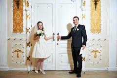 新娘和新郎在婚礼大厅附近的门 免版税库存照片