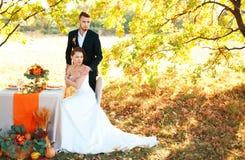 新娘和新郎在婚礼桌上 秋天室外设置 免版税图库摄影