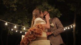 新娘和新郎在婚宴喜饼附近 夫妇切了土气的婚宴喜饼 室外 股票录像
