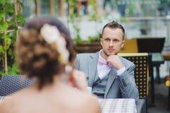 新娘和新郎在室外的咖啡馆 免版税库存照片